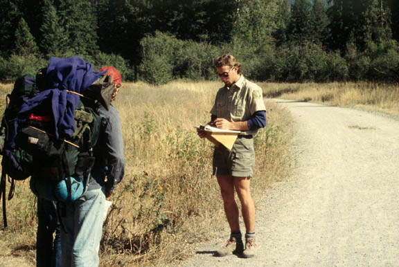 A backpacker and an agency staff member interact along a trail. The area's grasses appear to be very dry while the trees in the distance are quite green.