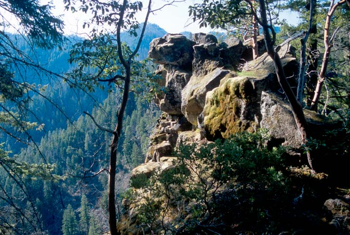 Looking past a large rock outcropping, to dense forested hills far below.