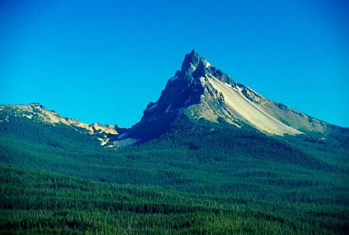 Mt. Thielsen, a single sharp peak, juts out of thick green conifer forest.