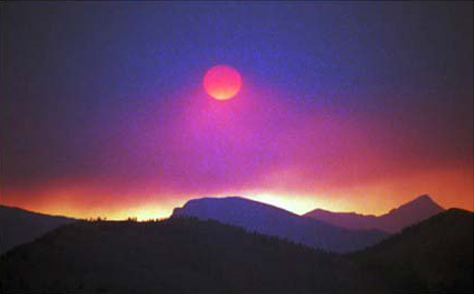 An eerie smoky image of a pink sun on a background of blue cloud, casting gold light over jagged peaks along the black horizon.