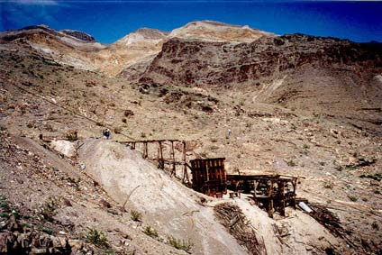 The remains of an abandoned mining operation sit high on a barren slope, surrounded by rock faces and gray talus.