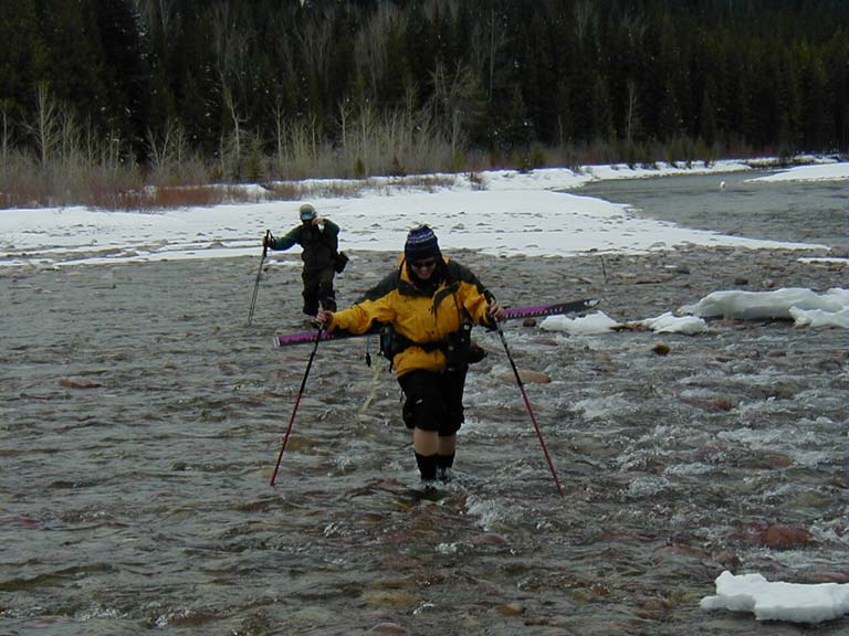 Two people with skis strapped to their backs, wade across the icy waters of a shallow river.
