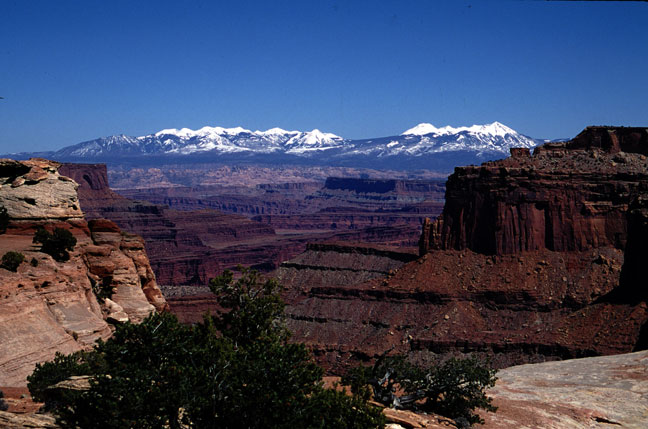 Looking down a canyon basin, high rock faces framing a view of high snowcapped mountains in the distance.