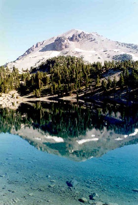 A tall rocky peak with large evergreen trees around its base, reflected on the mirror surface of a crystalline alpine lake.