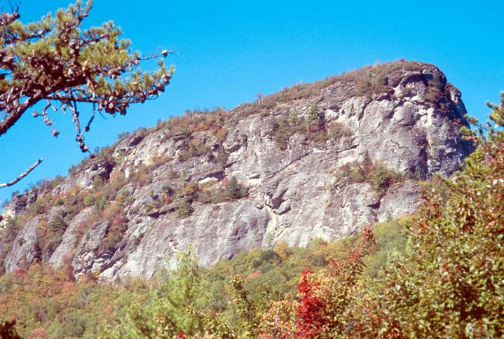 A high rocky knob rises vertically above the woodland trees below, in faint autumn color.