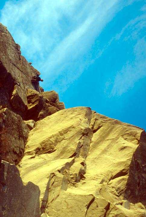 A lone rock climber clinging to a high rock face, high above a jagged sandstone face, under a blue sky.