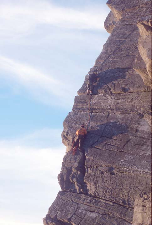 Two rock climbers clinging to cracks on a smooth face, with nothing but sky beyond.