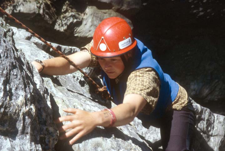 Looking down on a teenage girl in a red helmet climbing a rock face.