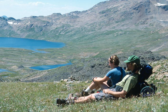 Two hikers resting on a grassy pass, overlooking a large alpine valley with several small lakes, far below.