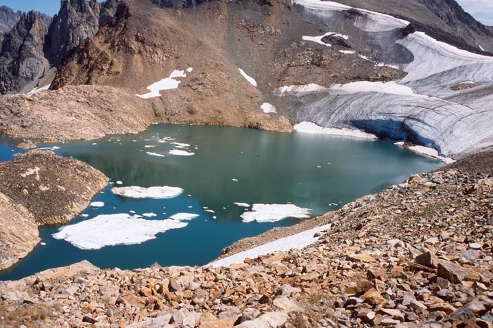 A single alpine glacial lake with floating patches of ice, feeding off a small glacier bordered by bare rocky slopes.