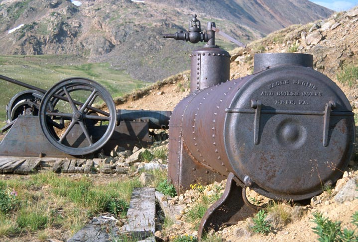 A large piece of abandoned mining equipment, sitting high in an alpine valley.