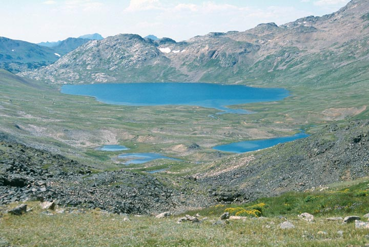 A large alpine bowl of low green tundra, surrounding a large blue lake, and several small ponds.