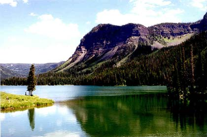 Looking over the placid green waters of an alpine lake surrounded by forest. A rocky face rises above the forest on the far shore.