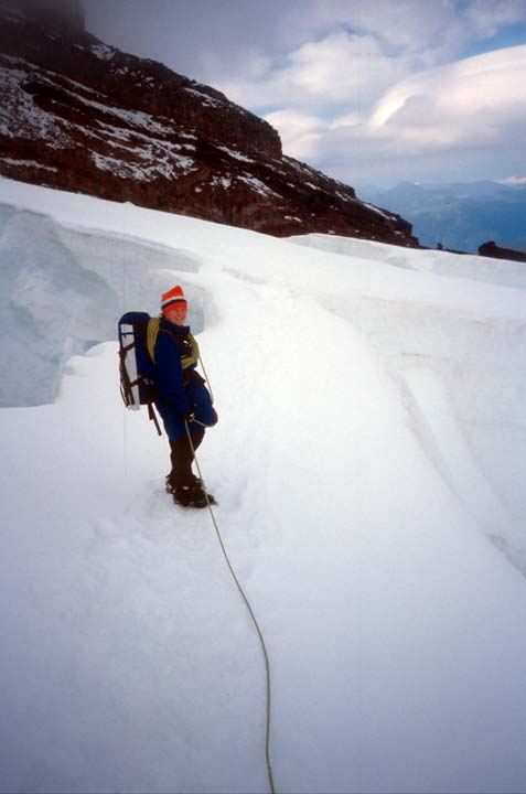 A climber with a large backpack, trailing a rope across a narrow snow bridge over a glacier.