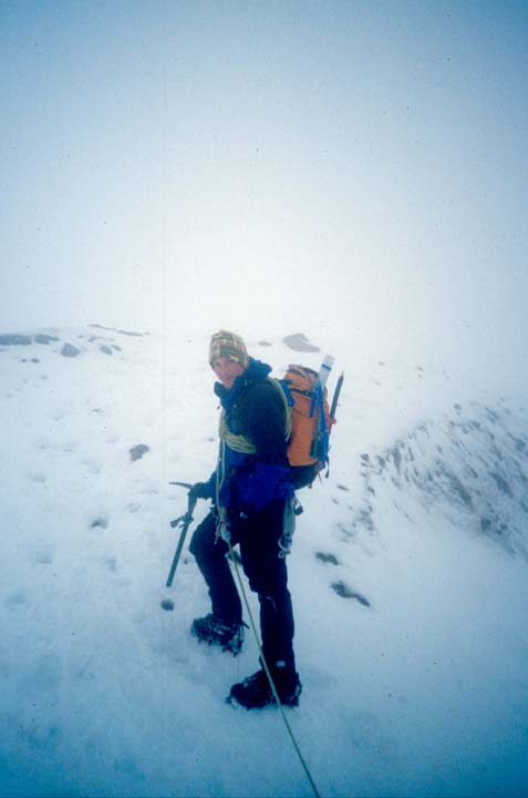 A climber with full gear, ascending a snow covered slope in white-out conditions.
