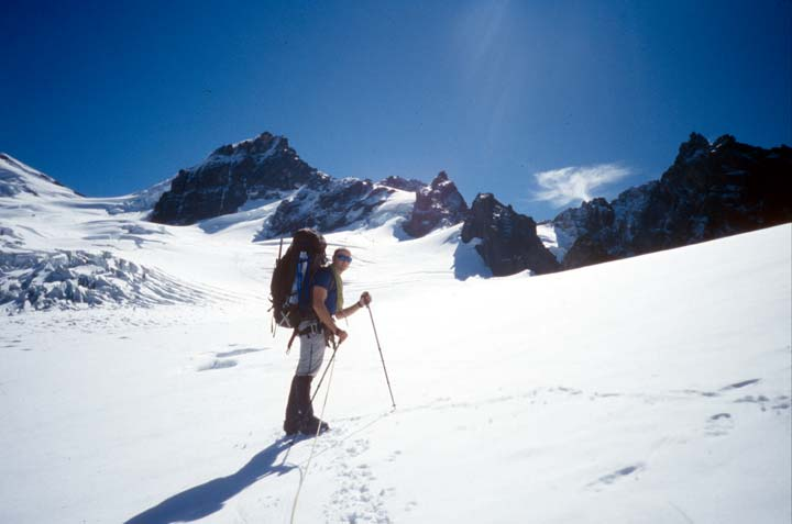 A lone climber with a large backpack, stands in the middle of a wide ice field, surrounded by jagged peaks.