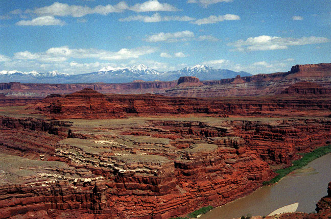 A section of brown river, lazily flowing along low sandstone faces, surrounded by higher canyon walls beyond, and even higher snowcapped peaks in the distance.
