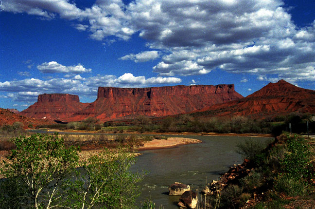 A wide stretch of river flowing through a valley surrounded by low brush, with high red sandstone columns bordering the drainage, under a sky filled with puffy white clouds.
