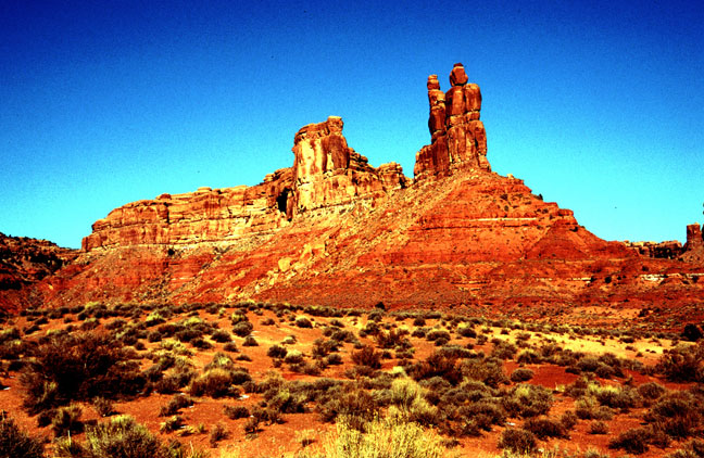 Open desert freckled with green brush, towered over by a high sandstone column, rising from a small ridge.