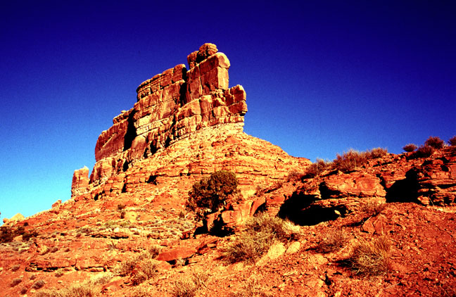 Bright red sandstone pillars tower high over the landscape, against a background of deep blue sky.
