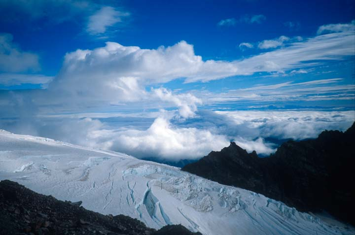 An almost abstract image of textured glacier ice torn by jagged black rocky pinnacles, under a blue sky streaked with wispy clouds all the way to the horizon.