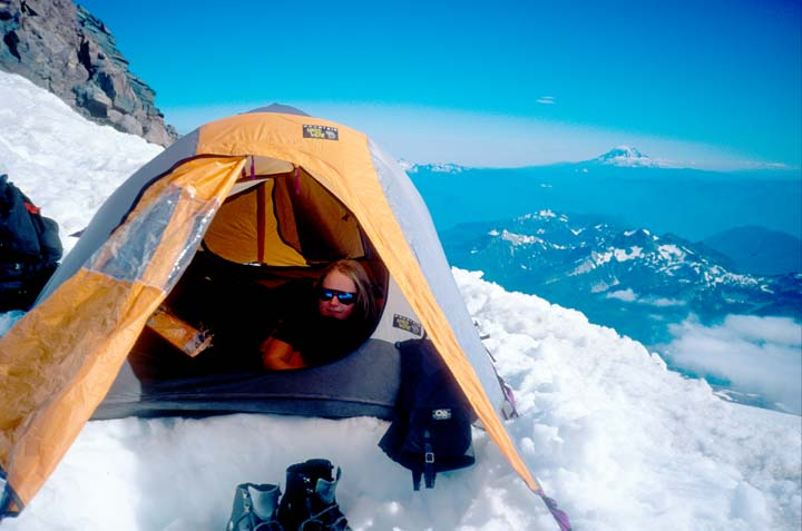 A girl peaks out of the door of a yellow tent perched on a snowfield high on Mount Rainier.