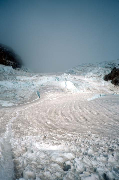 A sweeping glacier arm of gray snow and blue ice, leading away into swirling cloud far above.