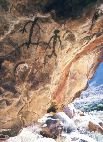 Two ancient drawings of black stick figures, decorate the brown sandstone walls of a cave.