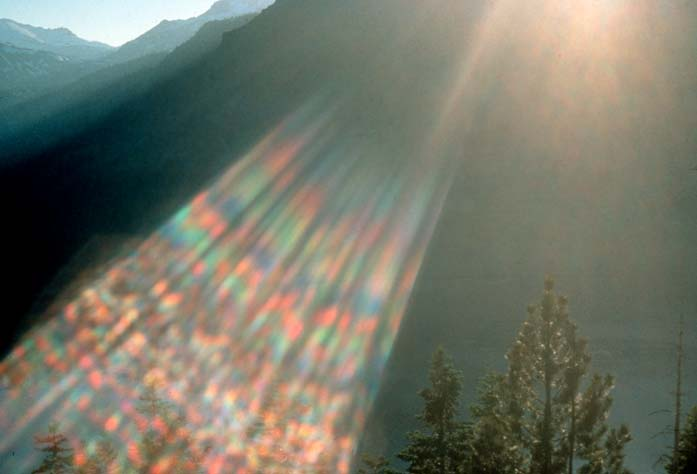 Looking over trees into a shadowed valley with a rainbow lens flare filling the frame.