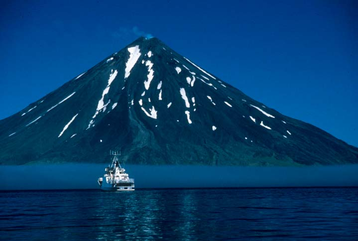 A large cone-shaped volcano rising directly out of the blue water, with a small plume of steam rising from its top. A large white ship sits nearby, on a background of low gray fog.