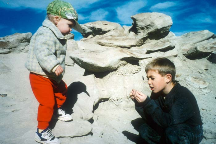 Two young boys look closely at the unique rock formations surrounding them.