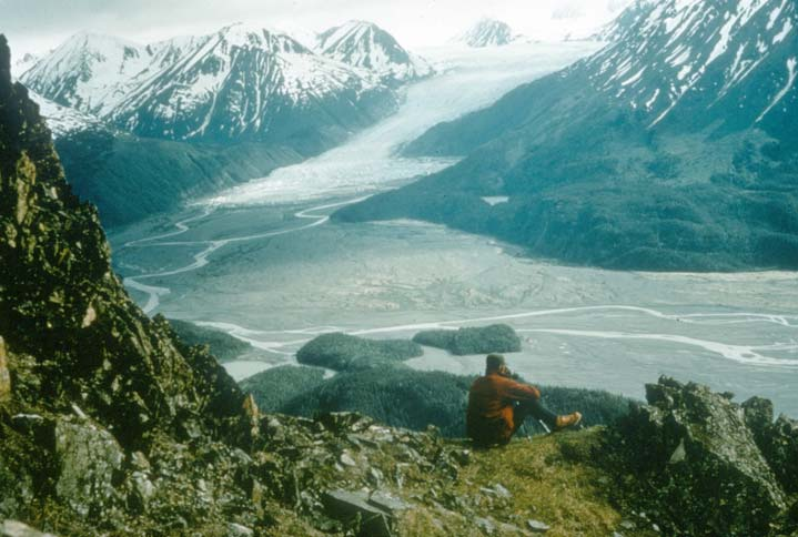 A lone hiker in a red jacket sitting high on a point overlooking a massive river valley feeding from an immense glacier.