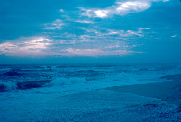A blue shadowed scene of waves crashing in on a sandy beach, with broken clouds above.
