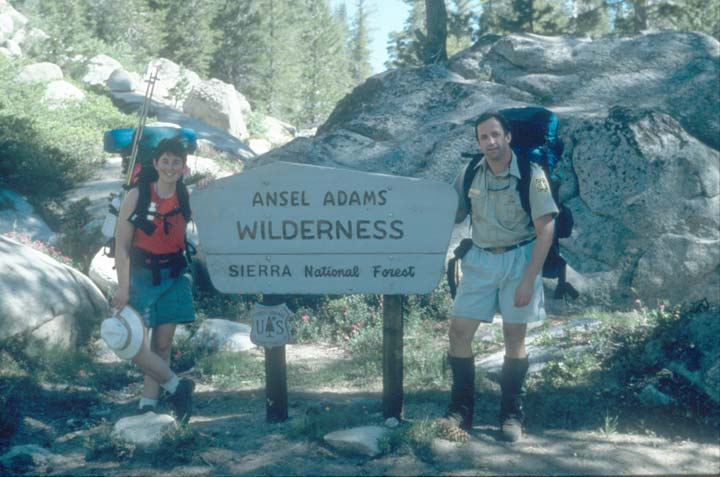 Two backpackers standing next to a large wilderness signpost.