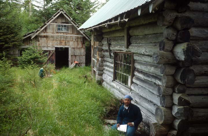 A man sitting in tall green grass, near the corner of an old log cabin.
