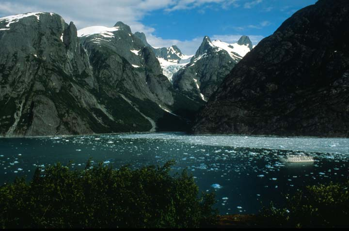 A large white boat navigating through a massive fjord filled with ice. Rugged peaks of bare rock rise from the water, decorated with hanging glaciers high above.