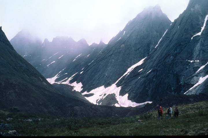 Three hikers in the distance crossing the grassy tundra with massive jagged peaks rising beyond, laced with snow and veiled by cloud.