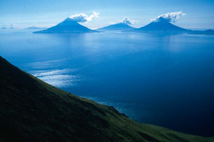 Three, steaming, volcanic islands protrude from the ocean far below.