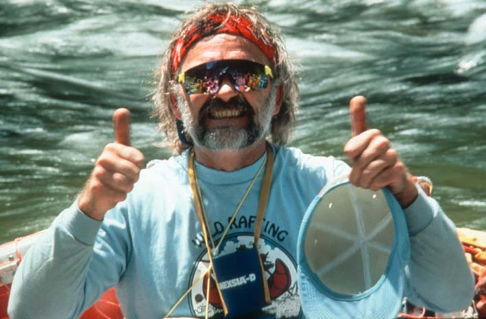 A close-up of a man giving a thumbs-up, with a river flowing in the background.
