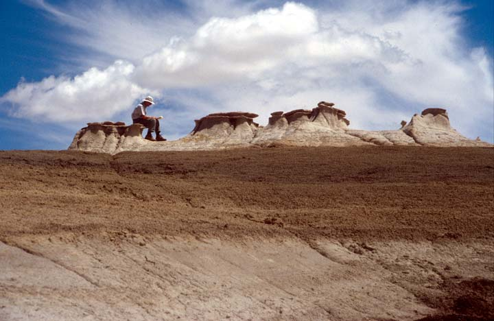 A researcher scribbles on a notebook while sitting on a hoodoos -- columnar, weathered, unusually-shaped rocks.