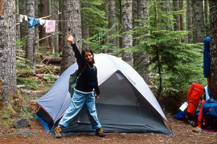 A young girl energetically raising her hand, standing in front of a tent in a forest campsite.