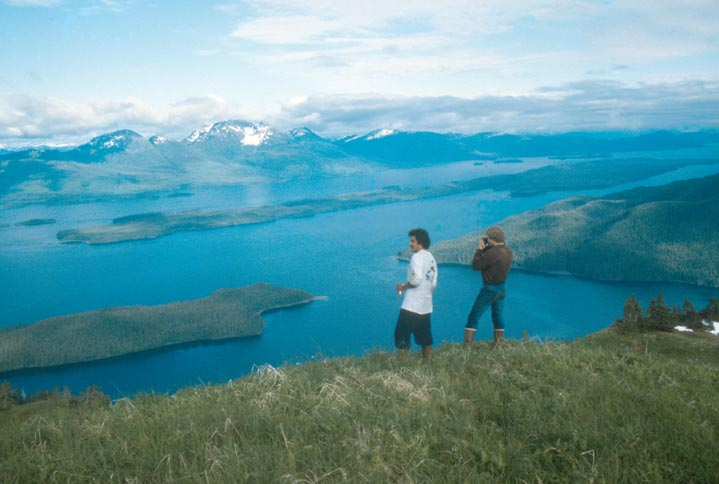 Two people standing high on a grassy slope, overlooking a coastline and large islands below.