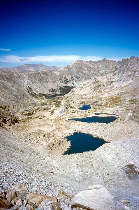 Three small lakes lie in the base of a barren alpine bowl, surrounded by gray rock and jagged ridges above.