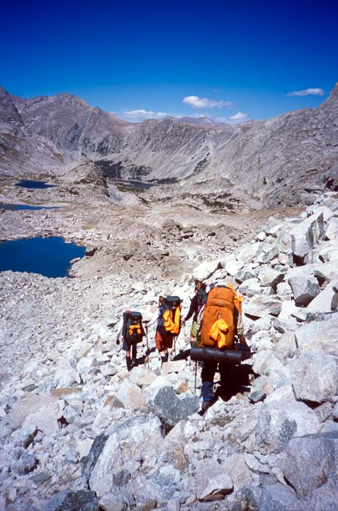 Three climbers with orange backpacks, navigate towards the valley floor along a slope of jumbled boulders and loose talus.