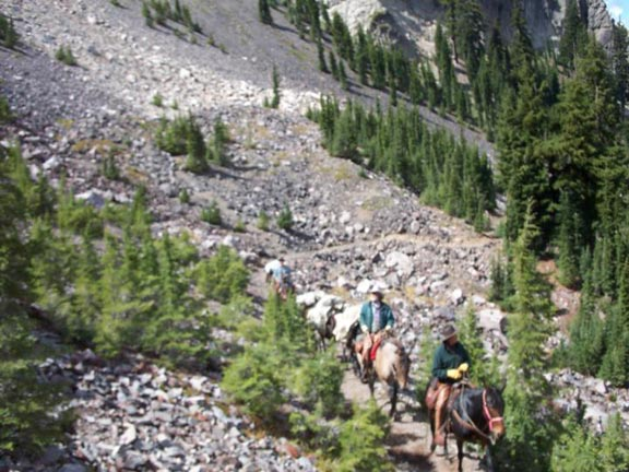 Three people on horseback, navigating a narrow trail along a rocky slope, dotted with sparse clumps of evergreen trees.