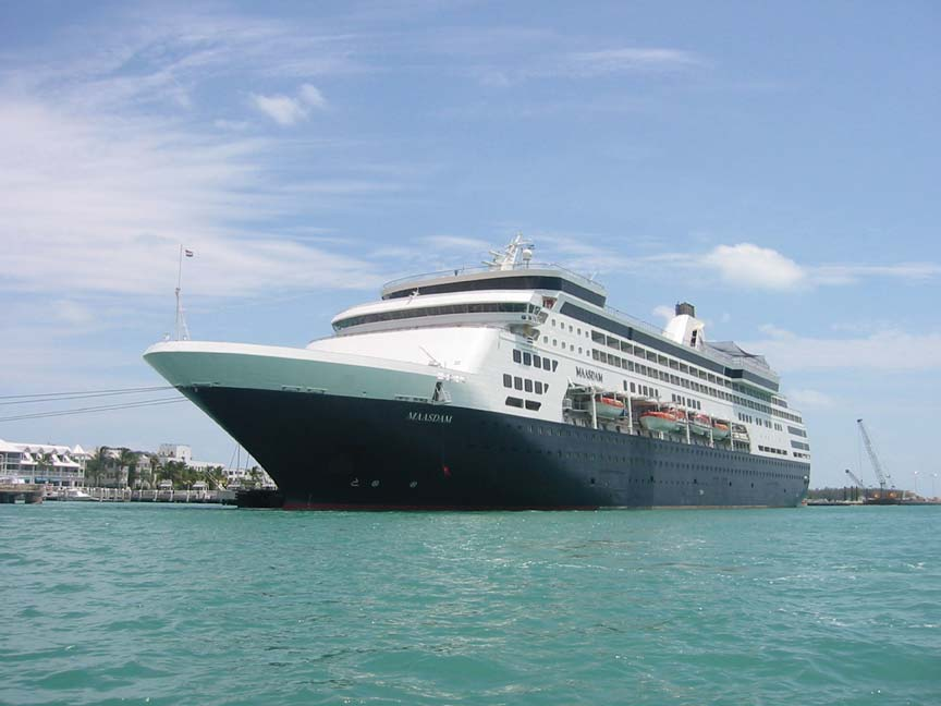A massive cruise ship with a black hull, docked in turquoise water, under a blue sky.