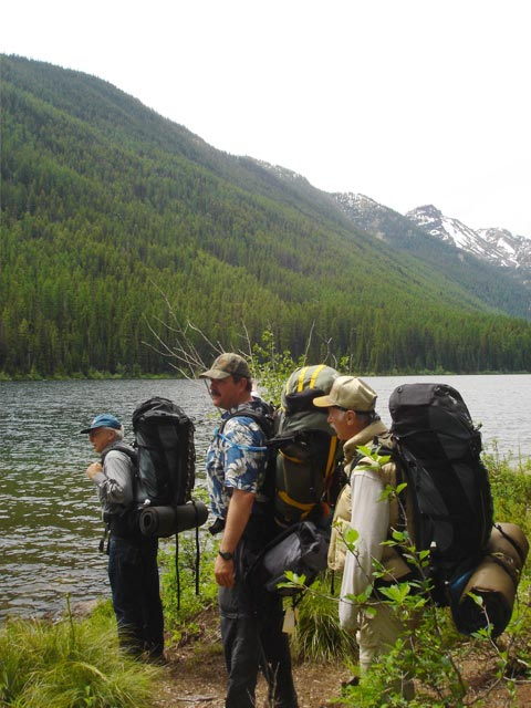 Three men wearing large backpacks, stand along the edge of a lake, looking across to the forested slope beyond.