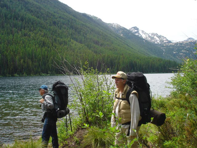 Two men wearing large backpacks, standing along the edge of lake with high forest slopes on the far side.
