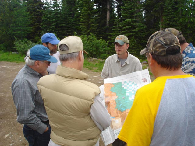 A small group of men standing in a small clearing along the forest, examining a map.