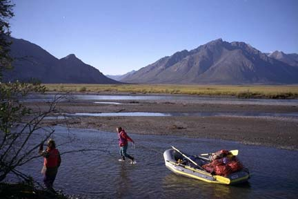 Two men pulling a large raft loaded with gear, up a shallow river. Tall mountains rise in the distance across the arctic tundra.